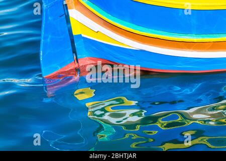 Reflections of stern of luzzo traditional fishing boat, Marsaxlokk, Malta