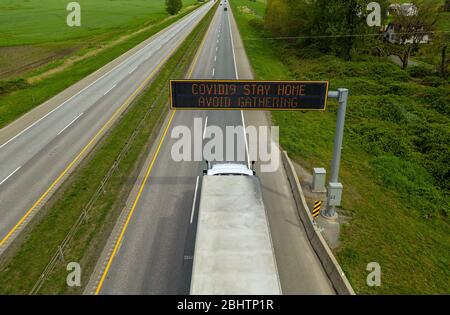 Elevated view of an electronic message board over the Trans-Canada Highway in British Columbia, Canada, advises people to Stay Home, Avoid Gathering, - Stock Photo