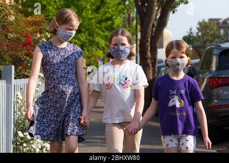 Three young sisters aged five years, 8 years & 10 years wearing masks that they've made at home with mum to wear during the COVID-19 / COVID 19 coronavirus pandemic of 2020; homemade face mask. UK. (118) - Stock Photo