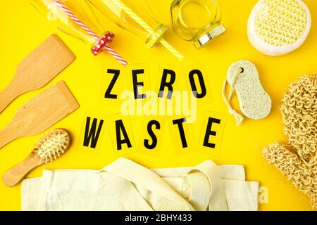 Zero waste concept. Textile eco bags, glass jars, wooden hair brush and washcloth and on yellow background with Zero Waste black text in center.
