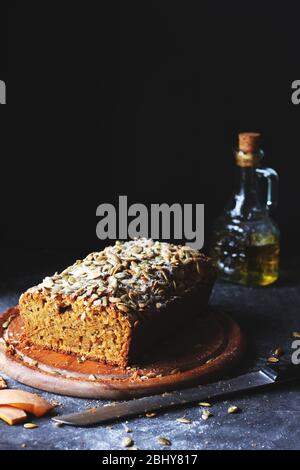 Homemade Pumpkin Bread Sprinkled With Sugar and Pumpkin Seeds on a Wooden Plate with a Bottle of Olive Oil in the Background - Stock Photo