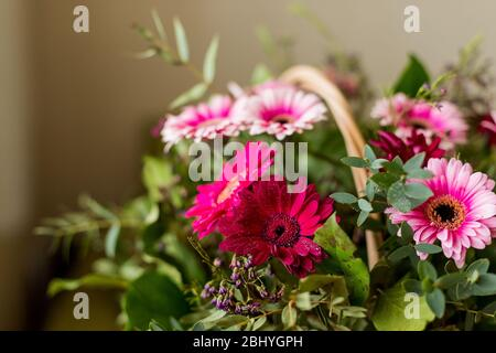 Happy Mothers Day gift of Spring Flowers on dark wood table and rustic dark red background. - Stock Photo