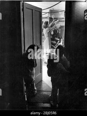 Mummy thought she would surprise the Children in the morning, but they thought otherwise and crept down the stair in their pyjamas to take a peep at the Christmas tree being decorated. - 21st December 1947 - Stock Photo