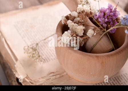 Old book with dry flowers in mortar close up