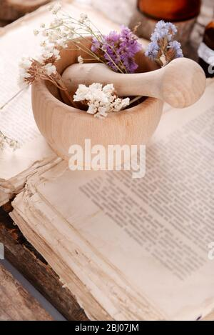 Old book with dry flowers in mortar close up Stock Photo