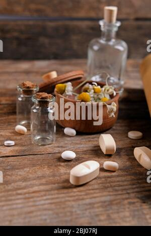 Dry flowers in mortar with tablets on table close up Stock Photo
