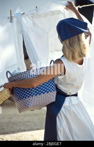 Hanging out the laundry on washing line in sunshine with a breeze - - Stock Photo