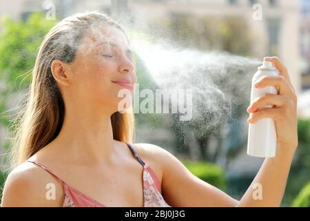 Young woman spraying Thermal Water on her face outside. Thermal water used for skin care, fix makeup, help skin irritation, redness and insect bites.