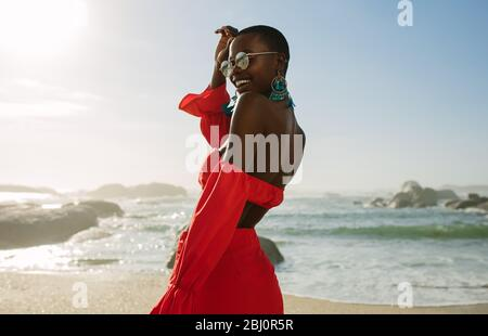 Beautiful african woman in red dress enjoying on the beach. Smiling female in beautiful dress walking along the shore. - Stock Photo