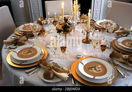 Formal festive table setting for holiday or wedding celebration with soup in large open bowls on gold edged plate on golden platters with candles and - Stock Photo