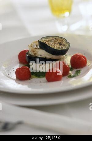 Starter of grilled aubergine slices layered with goat's cheese amd served with slightly roasted cherry tomatoes and pesto dressing on white plates in - Stock Photo