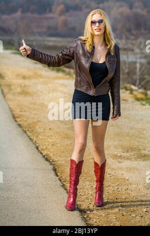 Teengirl hitchhiker on road hand finger thumb up thumbup - Stock Photo
