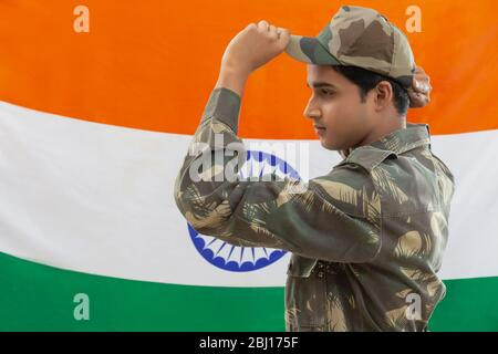 indian soldier proudly standing infront of national flag holding cap, independence day - Stock Photo