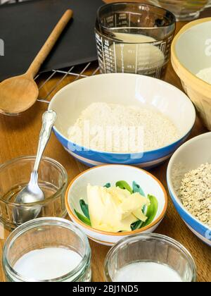 Ingredients for making oat bread on a kitchen table - Stock Photo