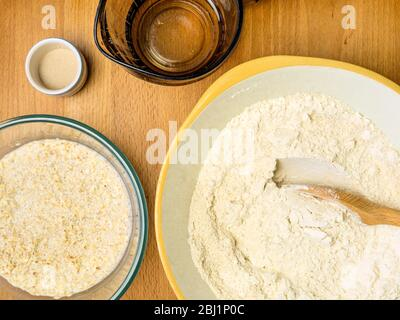 Mixing oat flour with strong white bread flour while soaking oats in oat milk with yeast and water for making oat bread - Stock Photo