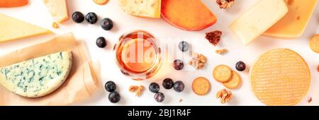 Cheese and wine tasting and pairing flat lay panorama on a white background with a place for text. Many different cheeses, shot from above - Stock Photo