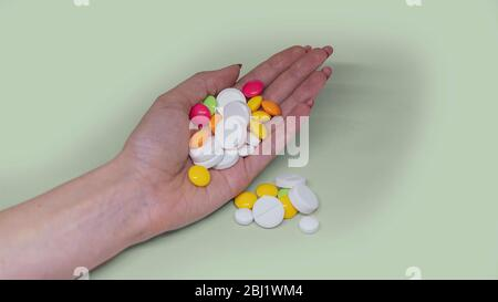 Young woman hand holding lots of pills and red tablets isolated on light green background - Stock Photo
