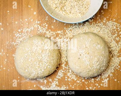Two rounds of oat bread dough rolled in oats on a wooden kitchen table with a bowl of oats - Stock Photo