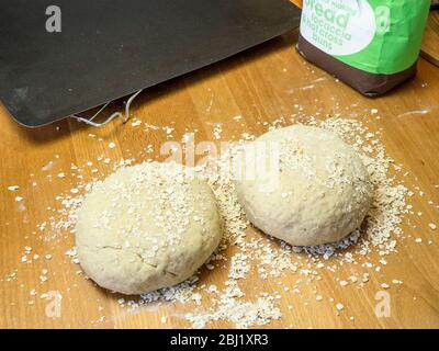 Two rounds of oat bread dough rolled in oats on a wooden kitchen table with a baking sheet and bag of flour - Stock Photo