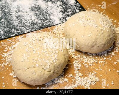Two rounds of oat bread dough rolled in oats with a floured baking sheet on a kitchen table - Stock Photo