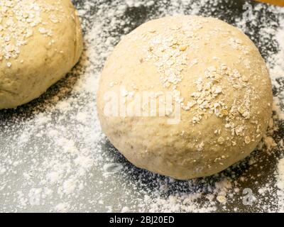 Two rounds of oat bread dough rolled in oats on a floured baking sheet on a kitchen table - Stock Photo