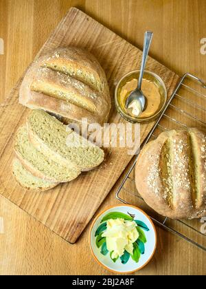 Freshly baked oat bread made with white bread flour and oat flour topped with rolled oats with honey and non dairy spread - Stock Photo