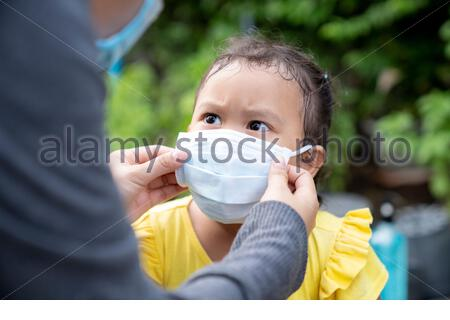 Rear of mother wearing a cloth mask for little girl protect herself from Coronavirus when child leave the house, illness or Air pollution concept. - Stock Photo