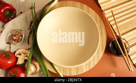 Round wooden board and plate, sauce and various vegetables on the table, wooden stick on a brown background. Flat lay. Copy space in the center of the - Stock Photo