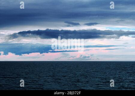 Sunset over White sea at dusk dramatic sky sunlight through clouds - Stock Photo