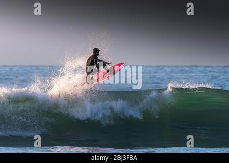 Spectacular surfing action as a surfer rides a wave in evening light at Fistral in Newquay in Cornwall. - Stock Photo
