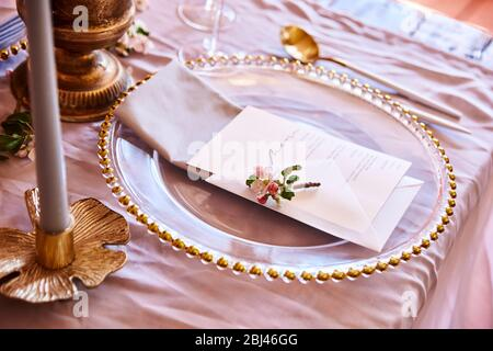 Festive table decor. Golden cutlery. With different natural colors and flowers. Garnet. Luxury wedding, party, birthday. View from above. Gold, pink. - Stock Photo