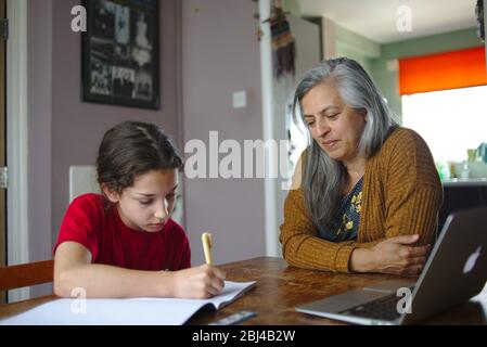Parent helping child with school work at home during coronavirus lockdown. April 2020 UK - Stock Photo