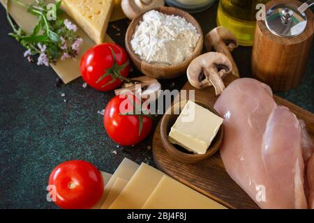 Food background italian. Ingredients for cooking lasagna with chicken and mushrooms on a dark stone background. Copy space. - Stock Photo