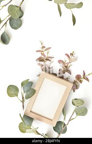 Desktop mock-up with blank paper card and branch leaf on white table background. - Stock Photo