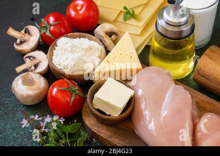 Food background italian. Ingredients for cooking lasagna with chicken and mushrooms on a dark stone background. - Stock Photo