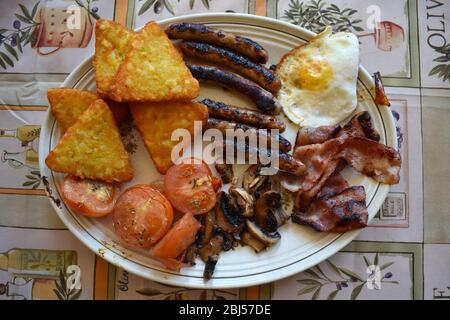 A full English breakfast served in UK and Ireland which includes bacon sausages eggs black pudding baked beans tomatoes mushrooms drinks coffee or tea - Stock Photo