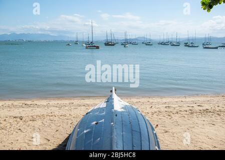 Upside-down wooden boat under the shade of a tree on the beach with several sailboats and boats moored on background. Bay with calm sea and no waves n - Stock Photo