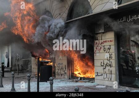 Tripoli, Lebanon, 28 April 2020. A branch of the arabic bank burns during riots that broke out following the death of a protestor shot by the army during protests triggered by economic collapse the previous night. Elizabeth Fitt Credit: Elizabeth Fitt/Alamy Live News - Stock Photo