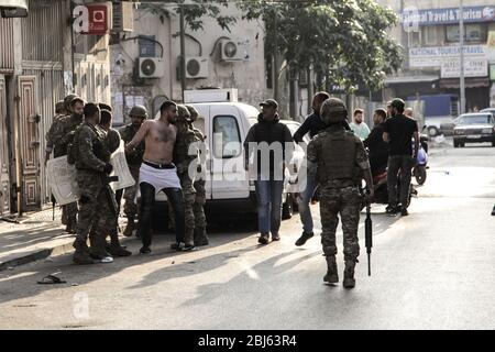 Tripoli, Lebanon, 28 April 2020. Soldiers apprehend a man during riots that broke out following the death of a protestor shot by the army during protests triggered by economic collapse the previous night. Elizabeth Fitt Credit: Elizabeth Fitt/Alamy Live News - Stock Photo