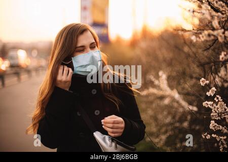 Happy young woman putting on face medical mask while standing on street in city during sunset in spring