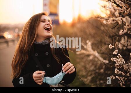 Happy cheerful young woman removing face medical mask while standing on street in city during sunset in spring