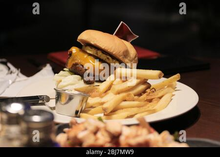 Classic burger with french fries and flag on top. - Stock Photo