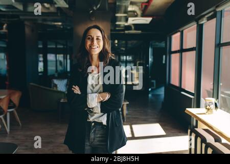 Confident businesswoman standing in office. Smiling woman standing with her arms crossed looking at camera. - Stock Photo