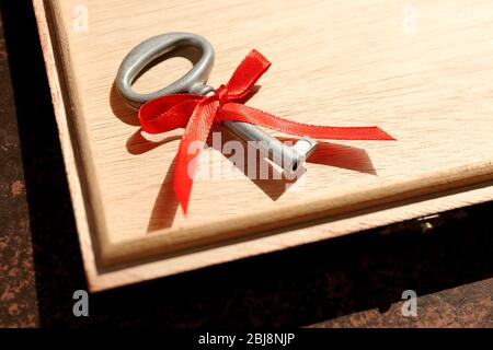 Vintage key in a wooden box with red ribbon. - Stock Photo