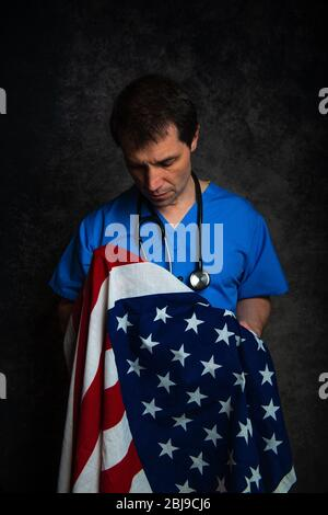 Sad/pensive male doctor in blue hospital scrubs with stethoscope, nursing the Stars & Stripes American flag close to his chest.
