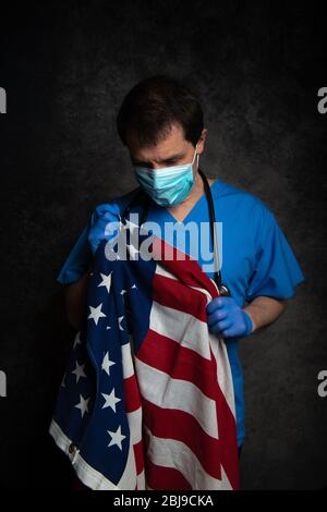Sad/pensive, male doctor in blue hospital scrubs with face mask and stethoscope, nursing the Stars & Stripes American flag close to his chest.