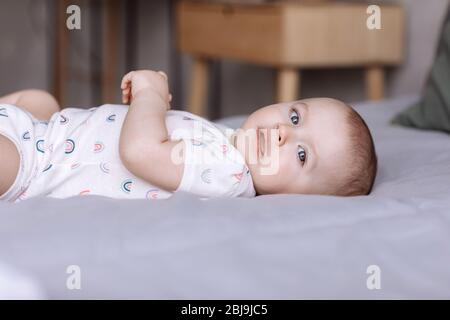 portrait of cute baby little girl lies on bed in the bedroom at home. concept of happy childhood