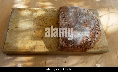 Freshly baked bread is ready to eat, it has been served on a wooden bread board - Stock Photo