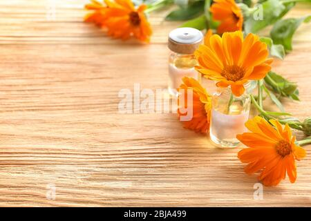Healing calendula flower in small glass bottle on light wooden background - Stock Photo