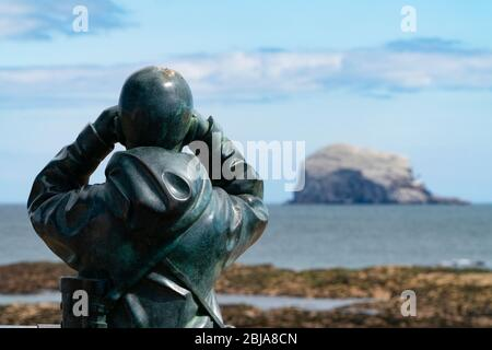View of sculpture called The Watcher by Kenny Hunter and Bass Rock in Firth of Forth from North Berwick, East Lothian, Scotland, UK - Stock Photo